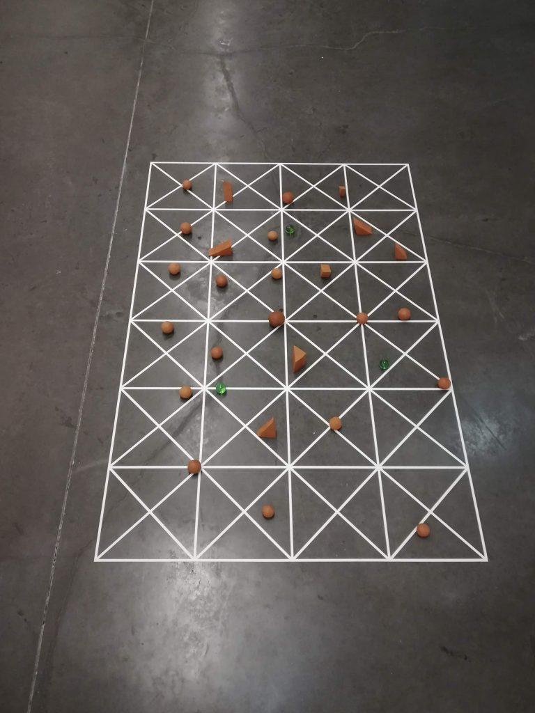 Mesa-oráculo, 2018 Vinil autocolante, barro e objectos vários Dimensão da grelha:  120x80 cm